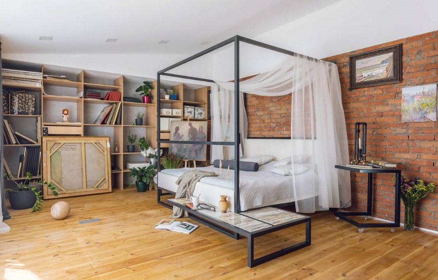 Спальная в стиле лофт: металлическая кровать, кирпичная стена, деревянный пол